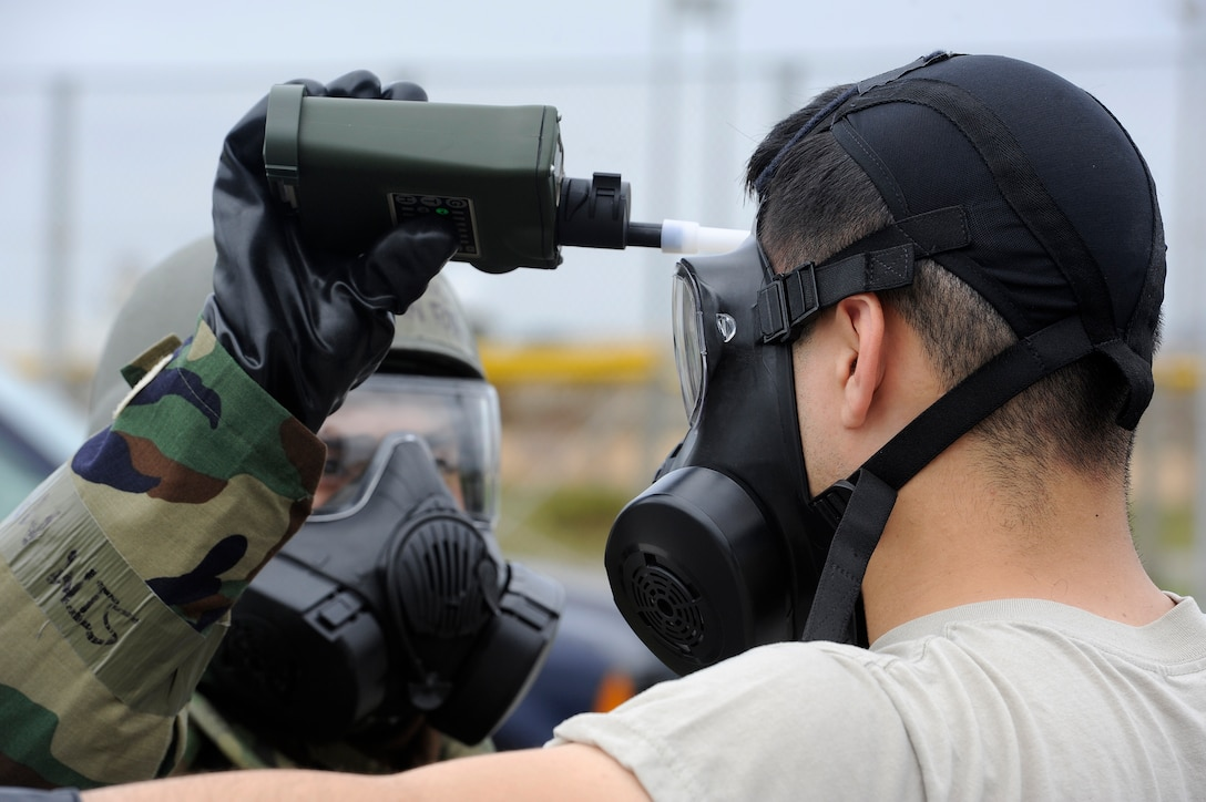 U.S. Air Force Airman 1st Class Ethan Fox, 18th Aircraft Maintenance Squadron, Chemical, Biological, Radiological, Nuclear and Explosives team member, uses contamination monitoring equipment on an Airman from the 18th Mission Support Group during Exercise Beverly High 15-2 on Kadena Air Base, Japan, April 22, 2015. The CBRNE team allowed the Airmen to quickly remove their simulated contaminated gear and get new gear to continue the mission. (U.S. Air Force photo by Staff Sgt. Marcus Morris)