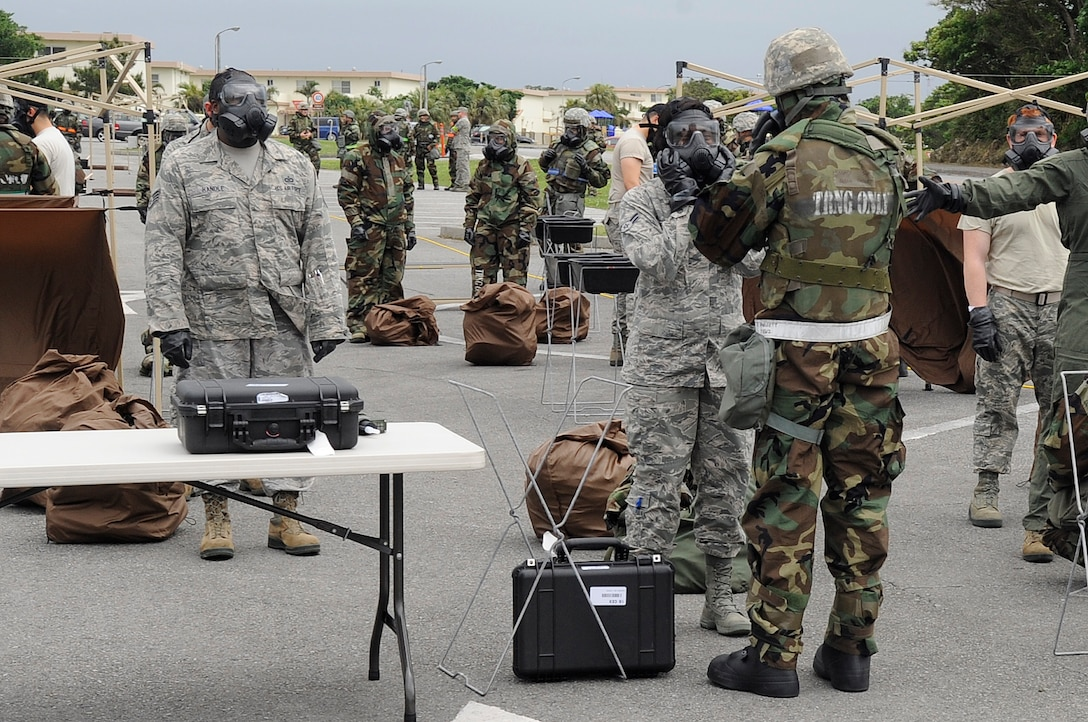 Airmen from the 18th Mission Support Group process through a contamination control area during Exercise Beverly High 15-2 on Kadena Air Base, Japan, April 22, 2015. A CCA consists of a hot zone, which is set up on the border of a contaminated area, a warm zone where Airmen are being decontaminated, and a cold zone which is a decontaminated area. (U.S. Air Force photo by Staff Sgt. Marcus Morris)