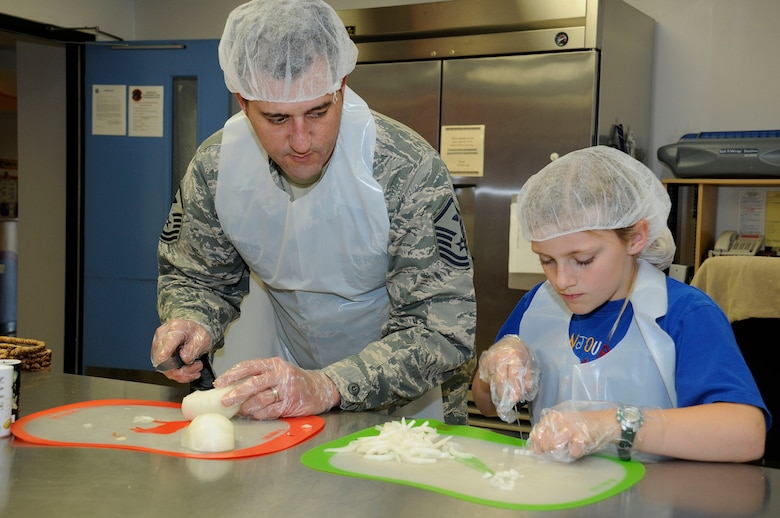 """Master Sgt. Zachary Pate, 61st ABG First Sergeant, participates with base housing children in the Home Cooking Club at the Youth Center at Fort MacArthur on April 16. The 61st Force Support Squadron offers a variety of activities throughout the year, but especially this month, as April is the """"Month of the Military Child."""" (U.S Air Force photo by Joe Juarez)"""