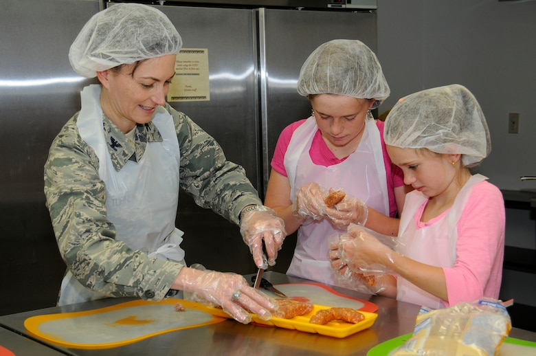 """Colonel Donna Turner, 61st Air Base Group commander, participates with base housing children in the Home Cooking Club at the Youth Center at Fort MacArthur on April 16. The 61st Force Support Squadron offers a variety of activities throughout the year, but especially this month, as April is the """"Month of the Military Child."""" (U.S Air Force photo by Joe Juarez)"""