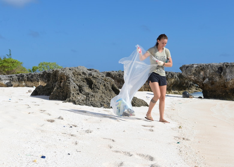 Senior Airman Stephanie Eck, 736th Security Forces Squadron, looks for trash to pick up along Scout Beach during an Earth Day beach cleanup April 18, 2015, at Andersen Air Force Base, Guam. The event was held in commemoration of Earth Day, an annual day where events worldwide are held to demonstrate support for environmental protection. (U.S. Air Force photo by Senior Airman Katrina M. Brisbin/Released)