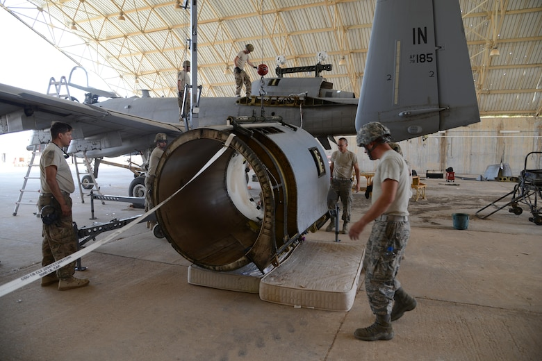 Airmen from the 332nd Expeditionary Maintenance Squadron remove a damaged nacelle, the protective covering on the engine, from an A-10C Thunderbolt II at Al Asad Air Base, Iraq. A maintenance response team from the 332nd EMXG repaired the jet and got it back in the air in less than five days after the jet suffered catastrophic engine failure and had to divert there. (U.S. Air Force photo by Tech. Sgt. Jared Marquis/released)