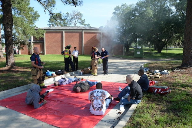 Marine Corps Logistics Base Albany firefighters/emergency medical technicians evaluate and provide medical treatment for burns and smoke inhalation to personnel as a result of a simulated fire at the Base Theater during the Raging Renegade active-shooter exercise, April 21. Installation Marines portrayed injured casualties for the exercise.