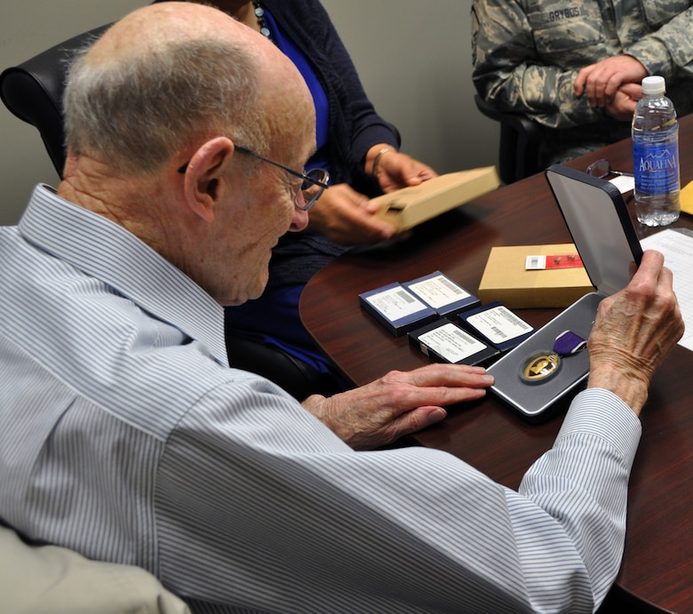 Former 1st Lt. Clayton A. Nattier, a veteran bomber pilot who was held as a prisoner of war during World War II, takes a look at the Purple Heart Medal received from the Air Reserve Personnel Center April 17, 2015, on Buckley Air Force Base, Colo. Nattier visited ARPC to receive his POW Medal among various other medals, then took time to personally meet and thank the members on the recognition service team who assisted him. Members from the ARPC recognition service team who assisted him are: retired Brig. Gen. Pat Quisenberry, evaluations branch chief, Jacqueline Bing, sustainment division chief, Master Sgt. Jeremy Bohn, pre-trained individual manpower division chief, and Master Sgt. Richard Grybos, NCO in charge of training and development. Nattier worked in conjunction with retired Lt. Col. Kathryn Wirkus, a constituent service representative from U.S. representative Ed Perlmutter's staff, to attain his POW Medal. A formal presentation to award the POW Medal to Nattier is currently being planned by U.S. representative Ed Perlmutter's office. (U.S. Air Force photo/Tech. Sgt. Rob Hazelett)