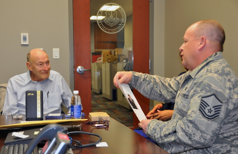 Former 1st Lt. Clayton A. Nattier, a veteran bomber pilot who was held as a prisoner of war during World War II, listens to Master Sgt. Richard Grybos, NCO in charge of training and development, during his visit to the Air Reserve Personnel Center April 17, 2015, on Buckley Air Force Base, Colo. Nattier visited ARPC to receive his POW Medal among various other medals, then took time to personally meet and thank the members on the recognition service team who assisted him. Along with Grybos, other members from the ARPC recognition service team who assisted Nattier are: retired Brig. Gen. Pat Quisenberry, evaluations branch chief, Jacqueline Bing, sustainment division chief, and Master Sgt. Jeremy Bohn, pre-trained individual manpower division chief. Nattier worked in conjunction with retired Lt. Col. Kathryn Wirkus, a constituent service representative from U.S. representative Ed Perlmutter's staff, to attain his POW Medal. A formal presentation to award the POW Medal to Nattier is currently being planned by U.S. representative Ed Perlmutter's office. (U.S. Air Force photo/Tech. Sgt. Rob Hazelett)