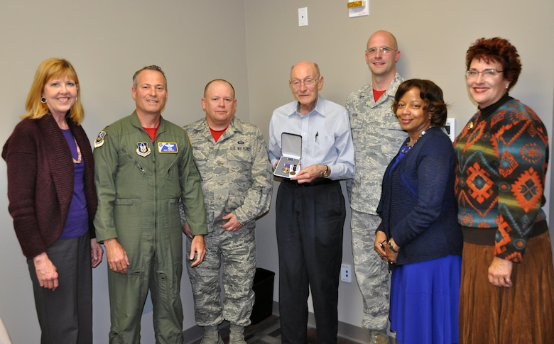 Former 1st Lt. Clayton A. Nattier, a veteran bomber pilot who was held as a prisoner of war during World War II, goes over the medals he received from the Air Reserve Personnel Center with Jacqueline Bing, sustainment division chief, April 17, 2015, on Buckley Air Force Base, Colo. Nattier visited ARPC to receive his POW Medal among various other medals, then took time to personally meet and thank the members on the recognition service team who assisted him. Along with Bing, other members from the ARPC recognition service team who assisted Nattier are: retired Brig. Gen. Pat Quisenberry, evaluations branch chief, Master Sgt. Jeremy Bohn, pre-trained individual manpower division chief, and Master Sgt. Richard Grybos, NCO in charge of training and development. Nattier worked in conjunction with retired Lt. Col. Kathryn Wirkus, a constituent service representative from U.S. representative Ed Perlmutter's staff, to attain his POW Medal. A formal presentation to award the POW Medal to Nattier is currently being planned by U.S. representative Ed Perlmutter's office. (U.S. Air Force photo/Tech. Sgt. Rob Hazelett)