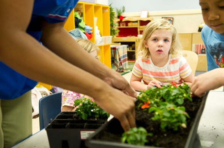 A child watches her classmates as they repot flowers at the Child Development Center II at Joint Base Andrews, Md., for Earth Day, April 22, 2015. The children repotted pansies and marigolds inside, with plans to plant sunflower seeds outside in the near future. (U.S. Air Force photo/Senior Airman Mariah Haddenham)