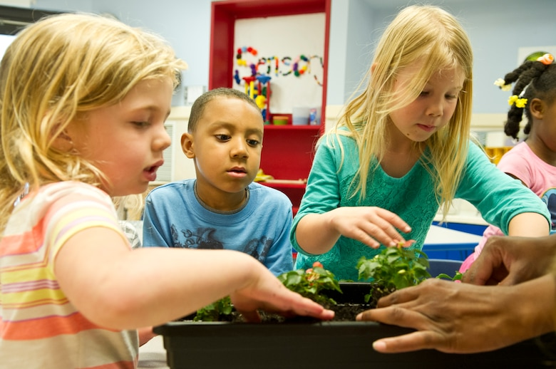 Children help each other repot flowers at the Child Development Center II at Joint Base Andrews, Md., for Earth Day, April 22, 2015. The children repotted the flowers with their teachers to learn more about plants and how they grow. (U.S. Air Force photo/Senior Airman Mariah Haddenham)