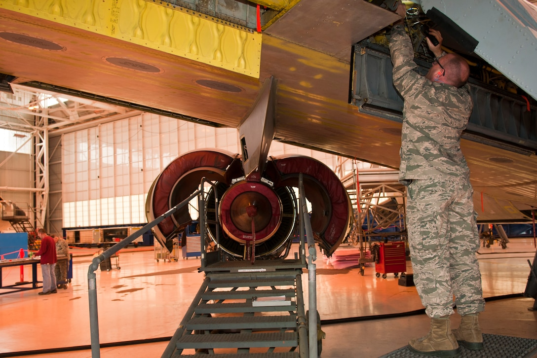 U.S. Air Force Master Sgt. Damon Drake, electrical and environmental specialist, 121st Air Refueling Wing, performs an inspection on a KC-135 Stratotanker during depot maintenance as part of Operation Team Spirit, Tinker Air Force Base, Okla., Mar. 2, 2015. The program teams unit maintenance Airmen up with depot facility personnel to perform inspections on aircraft as part of the depot maintenance process. (U.S. Air National Guard photo by Senior Airman Wendy Kuhn/Released)