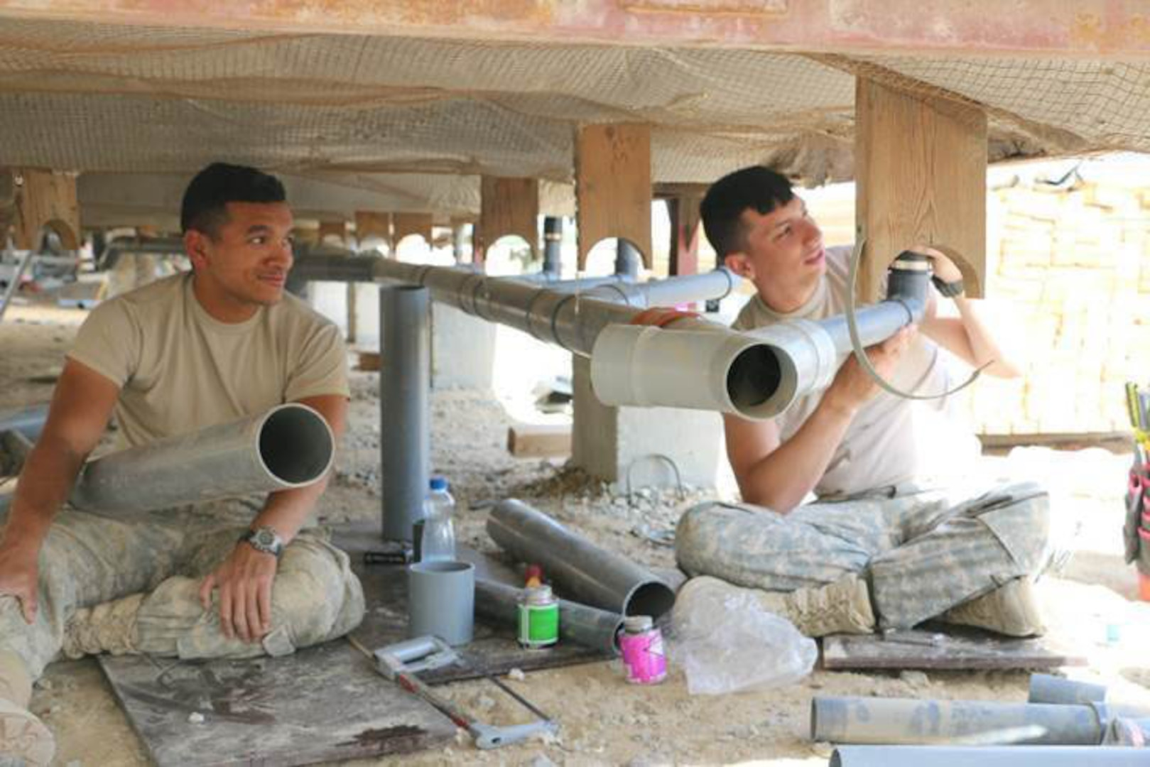Spc. Zenas Sigrah and Spc. Kevin Lucas work on installing pipe for plumbing in the support trailers recently at Camp Arifjan, Kuwait. The project was part of an effort to expand housing units for Soldiers assigned to Camp Arifjan. The base has seen its numbers increase with the drawdown in Afghanistan and the beginning of Operation Inherent Resolve in Iraq.