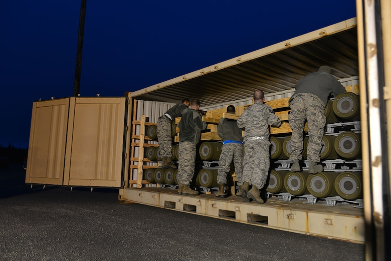 The first load of the ammunition barge arrives at Joint Base Elmendorf-Richardson, Alaska, April 15, 2015. Contracted forklift operators use their skills to unload each container, which weighs between 20,000 and 40,000 pounds. After the items are offloaded from the trucks, the ammunition inspection team standing by opens the containers and inspects the ammunition before storing it in earth-covered bunkers. (U.S. Air Force photo/Airman 1st Class Kyle Johnson)