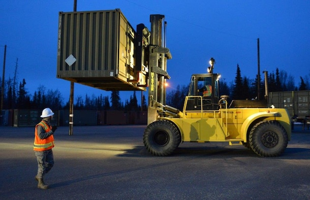 The first load of the ammunition containers arrive on Joint Base Elmendorf-Richardson, Alaska, April 15, 2015. Contracted forklift operators use their skills to unload each container, which weights between 20,000 and 40,000 pounds. After they are offloaded from the trucks, the ammunition inspection team standing by opens the containers and inspects the ammunition before storing them into earth-covered igloos. (U.S. Air Force Photo/Airman 1st Class Kyle Johnson)