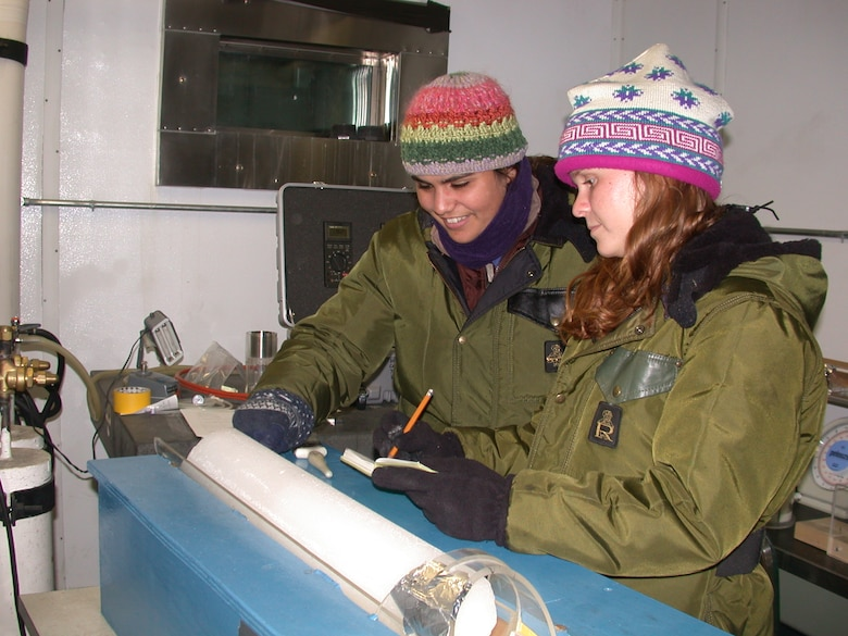 CRREL summer students Amanda Smith and Elyse Williamson examine an ice core from Greenland.