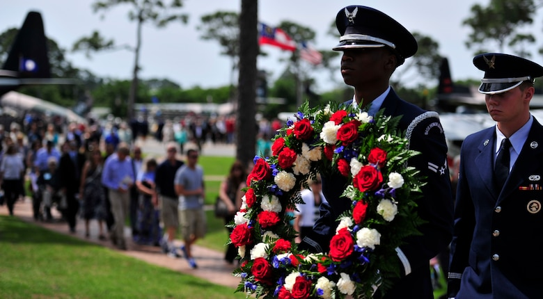 An honor guardsman carries a rose wreath from the air park to the base chapel during the Operation Eagle Claw memorial ceremony on Hurlburt Field, Fla., April 24, 2015.  The rose wreath honored Maj. Richard Bakke, Maj. Harold Lewis Jr., Tech. Sgt. Joel C. Mayo, Maj. Lyn McIntosh and Capt. Charles McMillan II, all from the 8th Special Operations Squadron, as well as Marine Sgt. John Harvey, Cpl. George Holmes Jr. and Staff Sgt. Dewey Johnson, who lost their lives during the operation. (U.S. Air Force photo/Staff Sgt. Melanie Holochwost)