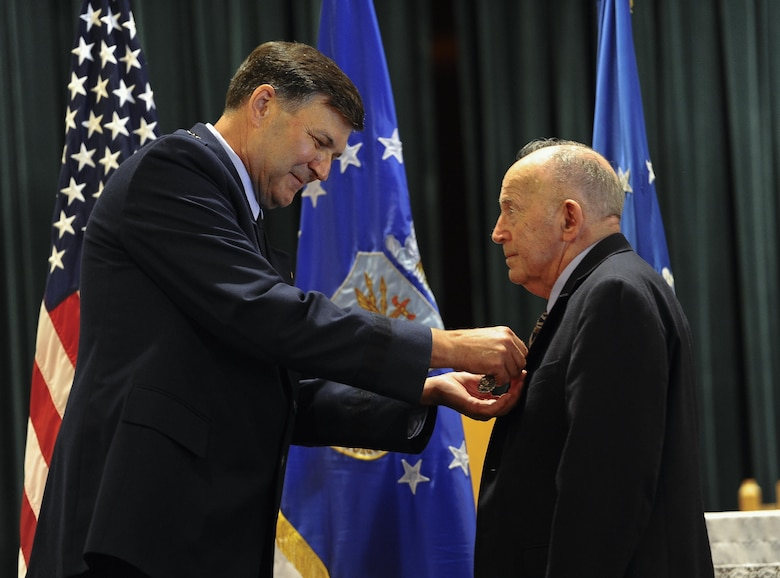 Lt. Gen. Brad Heithold, commander Air Force Special Operations Command, pins the Defense Superior Service Medal on Retired Air Force Col. Thomas Wicker at the base chapel on Hurlburt Field, Fla., April 24, 2015. (U.S. Air Force photo by Airman Kai White)