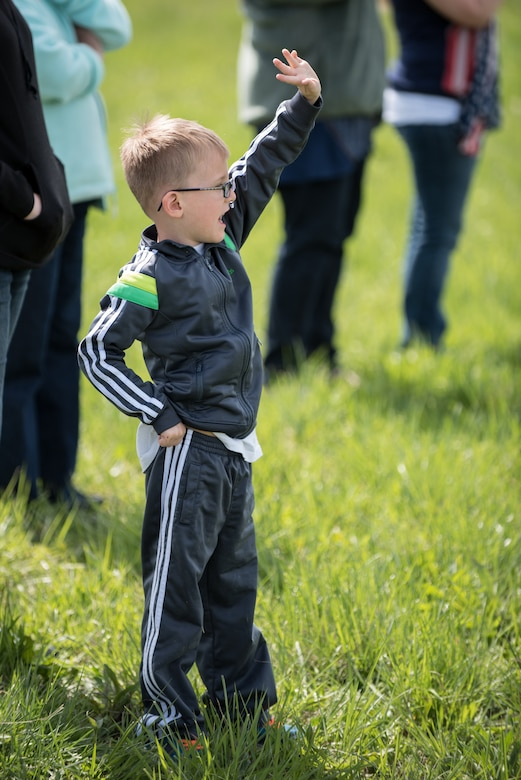 Asher Pentecost, son of Tech. Sgt. Donnie Pentecost of the 123rd Airlift Wing, waves goodbye to his father at the Kentucky Air National Guard Base in Louisville, Ky., April 24, 2015, as a C-130 Hercules aircraft caring more than 40 Airmen departs for deployment to an undisclosed air base in the Persian Gulf region. The Air Guardsmen will support airlift missions throughout the U.S. Central Command Area of Responsibility as part of Operation Freedom's Sentinel, which provides military training and counterterrorism capabilities in Afghanistan. (U.S. Air National Guard photo by Maj. Dale Greer)