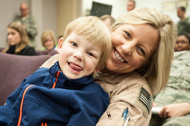 Maj. Jenn Helton, a C-130 navigator in the 123rd Airlift Wing, and her son, Kaiden Helton, attend a briefing at the Kentucky Air National Guard Base in Louisville, Ky., April 24, 2015, prior to Helton's deployment to an undisclosed air base in the Persian Gulf region. Helton and more than 40 other Kentucky Air Guardsmen comprise the third rotation of 123rd Airmen to deploy to the base since February. They will fly airlift missions throughout the U.S. Central Command Area of Responsibility in support of Operation Freedom's Sentinel, which provides military training and counterterrorism capabilities in Afghanistan. (U.S. Air National Guard photo by Maj. Dale Greer)