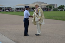 Col. Edwards presents King Rey Feo LXVII with the 2015 Fiesta Medallion during the Fiesta Military Parade at JBSA Lackland, 17 April 2015.