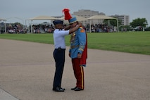 Col. Edwards presents King Antonio XCIII with the 2015 Fiesta Medallion during the Fiesta Military Parade at JBSA Lackland, 17 April 2015.