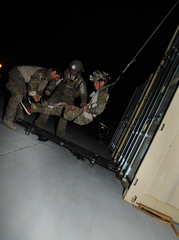 U.S. Air Force Pararescuemen, 48th Rescue Squadron, position a simulated patient on a gurney while the patient is lowered from the top of a conex during a pre-deployment training exercise at Davis-Monthan Air Force Base, Ariz., April 14, 2015. The exercise focused on mass casualty treatment, evacuation, extrication, confined space and collapsed structure rescue.  (U.S. Air Force photo by Senior Airman Betty R. Chevalier)