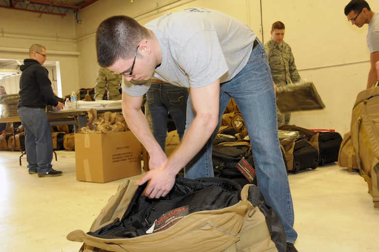 150308-Z-YW189-011 -- A 127th Wing Student Flight member prepares a mobility bag for an Airman of the 127th Wing who recently deployed to Southwest Asia. The deployment involved a total team effort around the wing. (U.S. Air National Guard photo by Staff Sgt. Samara Taylor)
