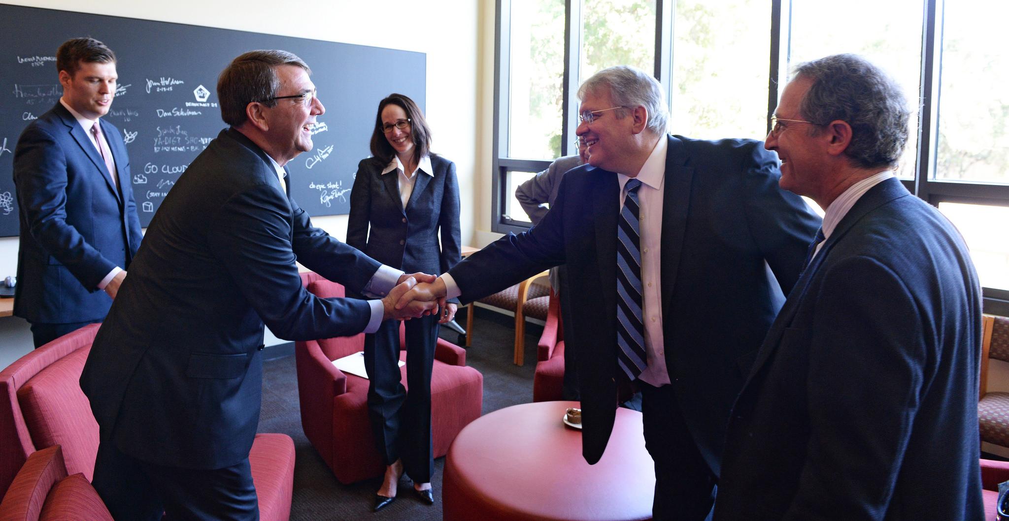 Defense Secretary Ash Carter, left, shakes hands with John
