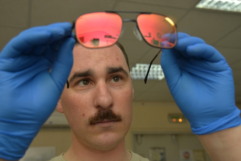 Staff Sgt. Scott ensures a pair of aircrew laser eye protection (ALEP) glasses is free from scratches and holds a tinted reflection at an undisclosed location in Southwest Asia April 15, 2015. ALEP's protect eyesight from high intensity lasers which are not visible to the naked eye. Scott is an aircrew flight equipment technician assigned to the Expeditionary Operations Support Squadron. (U.S. Air Force photo/Tech. Sgt. Christopher Boitz)