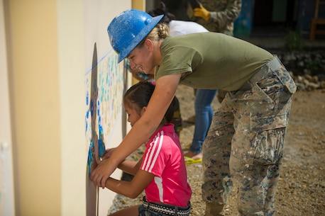 "TAPAZ, Philippines — U.S. Marine Lance Cpl. Dana Deline, assigned to the 9th Engineer Support Battalion, helps a schoolchild to paint her palm prints on a wall for a mural on a new school building at Don Joaquin Artuz Memorial Elementary School in Tapaz, Philippines, during Balikatan 2015, April 25. The two-classroom building is being constructed by U.S. Marine, Navy, and Armed Forces of the Philippines Army engineers as part of the Combined-Joint Civil-Military Operations Task Force on the island of Panay. Balikatan, which means ""shoulder to shoulder"" in Filipino, is an annual bilateral training exercise aimed at improving the ability of Philippine and U.S. military forces to work together during planning, humanitarian assistance and disaster relief operations."