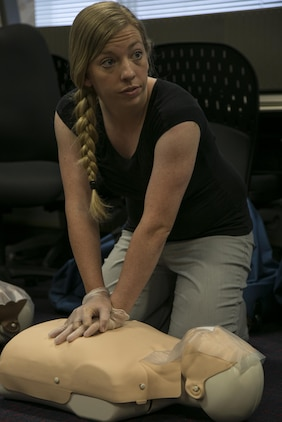 Hailey J. Day, financial official with G-6 communications Marine Corps Installations Pacific-Marine Corps Base Camp Butler, Japan, listens to instructions as she practices CPR during a class certifying Marines and Master Labor Contractors in adult, child and infant CPR, use of an automated external defibrillator and basic first aid in the Education Center April 22 on Camp Foster, Okinawa. CPR is a method used to maintain blood flow and brain function in an emergency situation such as a heart attack or drowning where the patient's heart beat or breathing has stopped.