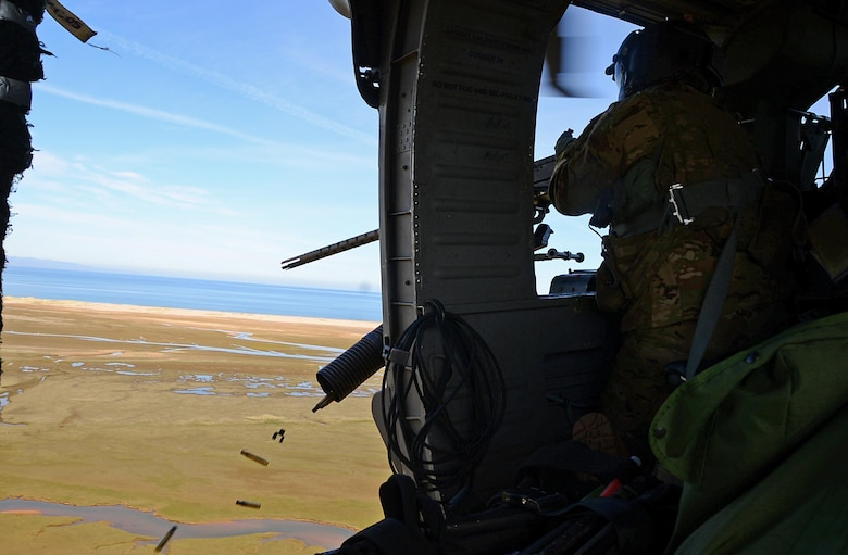 A special missions aviator assigned to Royal Air Force Lakenheath's 56th Rescue Squadron fires a .50-caliber machine gun out of an HH-60G Pave Hawk during exercise Joint Warrior 15-1 in Scotland, April 22, 2015. Airmen assigned to the 56th and 57th Rescue Squadrons participated in the multinational exercise to increase their readiness capabilities. (U.S. Air Force photo/Senior Airman Erin O'Shea)