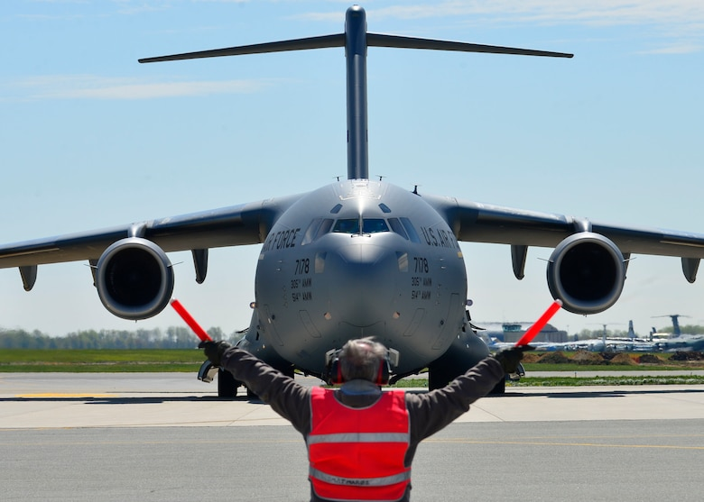 Bill Kennedy marshals a C-17 Globemaster III at Dover Air Force Base, Del., April 26, 2015. The aircraft was loaded with 69 members of the Fairfax County Urban Search and Rescue Team, their supplies and equipment, and six K-9s, to assist Nepal with rescue operations after the country was struck by a 7.8-magnitude earthquake. Kennedy is assigned to the 436th Aircraft Maintenance Squadron transit alert section. (U.S. Air Force photo/Airman 1st Class William Johnson)