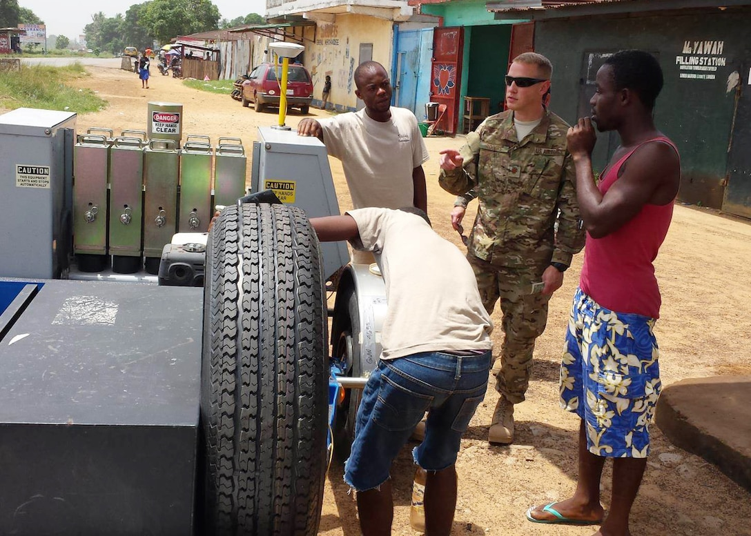 Maj. Robert C. Rogers, an Individual Mobilization Augmentee currently serving as the branch chief for the Air Force Civil Engineering Center's Airfield Pavements Evaluation team, buys gasoline in glass jars from a local gas station in Liberia. (Courtesy photo/Master Sgt. James Dixon)