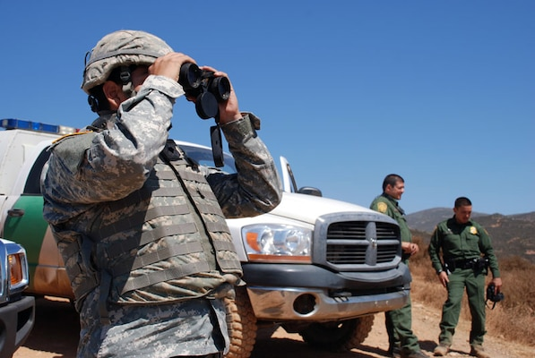 A California National Guard Soldier, left, works with U.S. Customs and Border Protection agents to scour the hills near the U.S.-Mexico border.