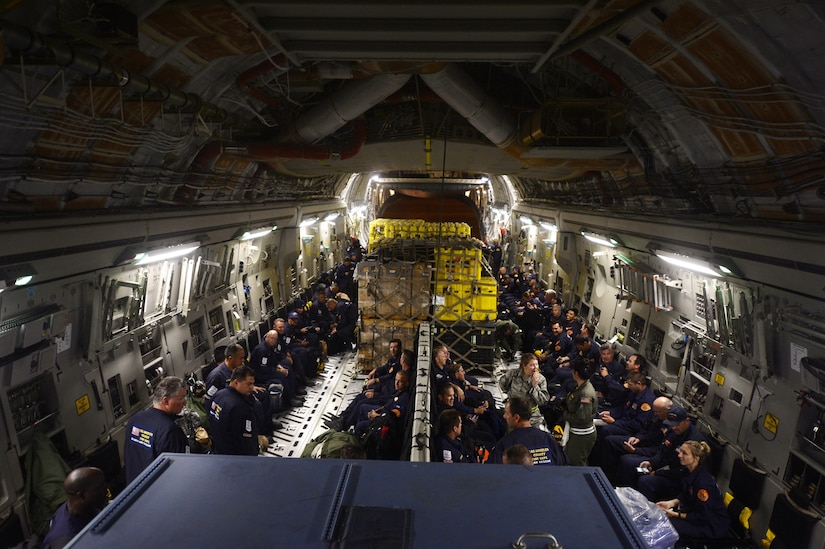 U.S. Air Force personnel load relief supplies for victims of the Nepal earthquake into a USAF C-17 Globemaster III from Joint Base Charleston, S.C., at March Air Force Base, Calif., April 26, 2015. The U.S. Agency of International Development relief cargo included eight pallets, 59 Los Angeles County Fire Department personnel and five search and rescue dogs. (U.S. Air Force photo by Airman 1st Class Taylor Queen/Released)