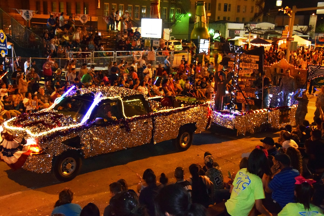 """The 433rd Airlift Wing's """"M*A*S*H"""" themed float moves through downtown San Antonio during the Fiesta Flambeau Parade, April 25, 2015. The parade's theme was """"Television: Then and Now,"""" and according to the Fiesta San Antonio program is """"America's largest illuminated night parade."""" Over 600,000 spectators lined the streets of San Antonio on a humid spring evening to see over 200 floats and marching bands perform in the grand finale of Fiesta Week. It is estimated 750,000 viewers (television and internet) watched this year's parade. (U.S. Air Force Photo/ Tech. Sgt. Carlos J. Trevino)"""