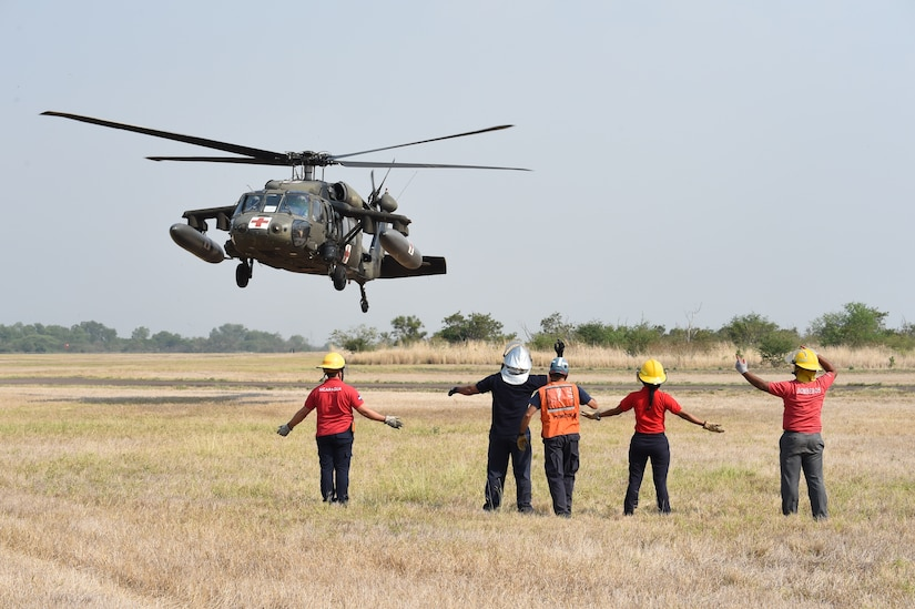 Firefighters hail an HH-60 Blackhawk as part of a simulated emergency rescue operation April 23, 2015, at Soto Cano Air Base, Honduras. The simulated rescue was part of the Central America Sharing Mutual Operations Knowledge and Experience exercise, designed to build partnership capabilities by bring firefighters from the U.S. and Central American countries together as a unified team. (Photo by Martin Chahin)
