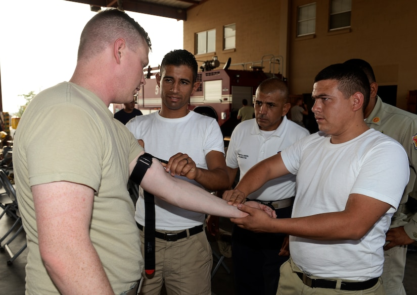Spc. Jeffrey Crenshaw, a Medical Element combat emergency medical technician, explains self-aid, buddy care concepts to Honduran firefighters April 21, 2015, at Soto Cano Air Base, Honduras. The instruction was part of the Central America Sharing Mutual Operations Knowledge and Experience exercise, which brought U.S. and Central American firefighters together to build partnership capacity by training on necessary lifesaving techniques. (U.S. Air Force photo by Staff Sgt. Jessica Condit)