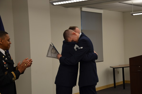 Airman Christian Frizzell, a Biomedical Equipment Technician (BMET) student at the Medical Education and Training Campus, hugs his father, Chief Master Sgt. Charles Frizzell after his dad presents him with his graduation certificate during his class graduation ceremony April 10. Airman Frizzell is starting his new career at Wright-Patterson Air Force Base, Ohio. His father, also a BMET, is currently assigned as the senior enlisted advisor to the commander at the 374th Medical Group at Yokota Air Base, Japan. (Photo by Lisa Braun)