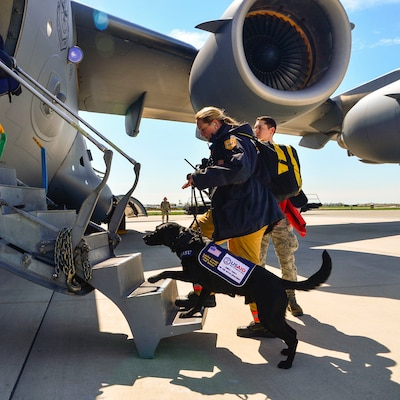 Jennifer Massey and her K-9 dog, Phayu, board a U.S. Air Force C-17 Globemaster III on Dover Air Force Base, Del., April 26, 2015, bound for Nepal. Massey is a Fairfax County Urban Search and Rescue K-9 search specialist from Fairfax, Va., serving as part of a 69-person search and rescue team deploying to Nepal to assist in rescue operations after the country was struck by a 7.8-magnitude earthquake. U.S. Air Force photo by Airman 1st Class William Johnson