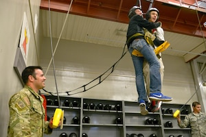 Air Force Junior ROTC students from Charles Francis Adams High School in Clarkston, Wash.,, are hoisted up by Staff Sgt. Ray C-Perez, 22nd Training Squadron Survival, Evasion, Resistance and Escape specialist, during a base wide tour April 22, 2015, at Fairchild Air Force Base, Wash. The hoist machine is used by students to train and practice before going out on the field and getting hoisted up onto the UH-1N Iroquois helicopter. (U.S. Air Force photo/Senior Airman Janelle Patiño)
