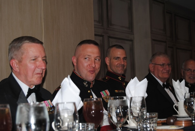 "President of the Mess and Recruiting Station Louisville Commanding Officer, U.S. Marine Corps Maj. Donald L. Hotchkiss ,center, conducts the traditional ""tasting of the beef"" during a mess night at the Campbel House Hotel in Lexington, Kentucky, March 28, 2015, in order to ensure the food is fit for human consumption. It is tradition that this piece of beef is tainted with copious amount of spices and heavily overcooked. (Courtesy photo by Marine Corps Coordinating Council Kentucky)"
