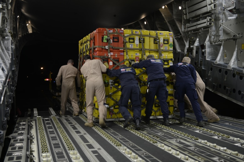 U.S. Air Force Airmen and members of the United States Agency to International Development (USAID) and Los Angeles County Search and Rescue team offload relief supplies for victims of the earthquake in Katmandu, Nepal, April 28, 2015. The Air Force transported relief supplies along with members of the United States Agency to International Development (USAID), the Los Angeles County Search and Rescue team and five search and rescue dogs to provide assistance to the men and women in Nepal. (U.S. Air Force photo/Airman 1st Class Taylor Queen)