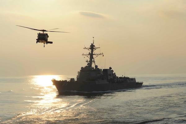 An MH-60S Knighthawk helicopter flies by the guided-missile destroyer USS Farragut during a replenishment-at-sea evolution in the Arabian Sea on Dec 4, 2012. U.S. Navy photo