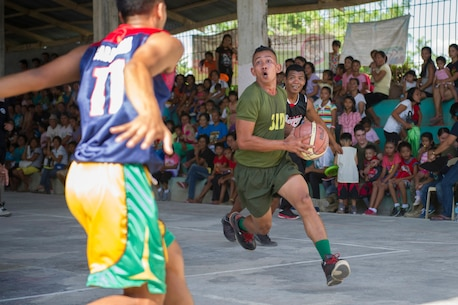 "An Armed Forces of the Philippines Army basketball player aims for a layup at a friendly basketball game between Barangay Taft basketball players and players from the Combined-Joint Civil-Military Operations Task Force on the island of Panay in Tapaz, Philippines, during Balikatan 2015, April 28. The goodwill game was held for some fun and entertainment following the conclusion of the combined U.S. and AFP force's humanitarian and disaster response activities on the island. Balikatan, which means ""shoulder to shoulder"" in Filipino, is an annual bilateral training exercise aimed at improving the ability of Philippine and U.S. military forces to work together during planning, humanitarian assistance and disaster relief operations."