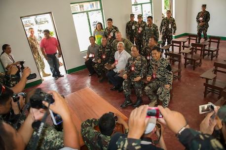 "U.S. armed forces, Armed Forces of the Philippines and local civic leaders sit at desks in a new classroom at Don Joaquin Artuz Memorial Elementary School built by AFP and U.S. engineers as part of the Combined-Joint Civil-Military Operations Task Force on the island of Panay in Tapaz, Philippines, during Balikatan 2015, April 27. The engineers worked together for 40 days to complete the Philippine Department of Education, modified one-story, two-classroom building. Balikatan, which means ""shoulder to shoulder"" in Filipino, is an annual bilateral training exercise aimed at improving the ability of Philippine and U.S. military forces to work together during planning, humanitarian assistance and disaster relief operations."