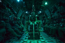 """U.S. Air Force Senior Airman Nicholas Oswald, a loadmaster, 374th Operations Support Squadron, Yokota Air Base, Japan, sits with Philippine air force aircrew members during a night flight, April 24, as part of exercise Balikatan 2015. Balikatan is a Filipino term that means """"shoulder to shoulder,"""" or """"sharing the load together,"""" and characterizes the spirit of the exercise, focusing on Philippine-U.S. partnership and commitment to the Mutual Defense Treaty."""