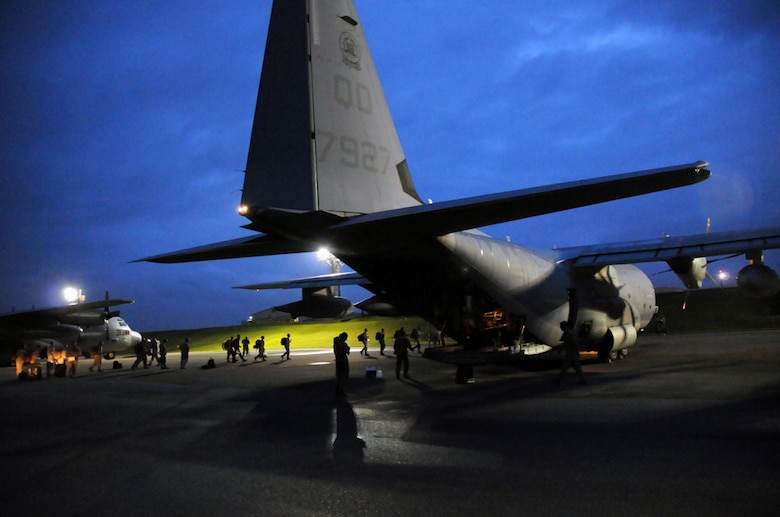 Members of a U.S. Pacific Command Joint Humanitarian Assistance Survey Team load onto a Marine Corps C-130 Hercules at Kadena Air Base, Japan, on April 29, 2015. The team deployed to Nepal to assist earthquake relief efforts. Kadena's Airmen worked through the night to load the team's 20-plus members and gear for the departure. (U.S. Air Force photo/2nd Lt. Erik Anthony)