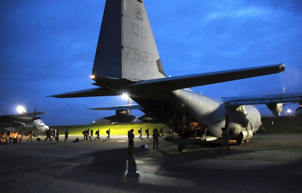 Members of a U.S. Pacific Command Joint Humanitarian Assistance Survey Team load onto a U.S. Marine Corps C-130 Hercules at Kadena Air Base, Japan, April 29, 2015. The team is deploying to Nepal to assist earthquake relief efforts. Kadena's Airmen worked through the night to load the team's 20-plus members and gear for the departure. (U.S. Air Force photo/2nd Lt. Erik Anthony)