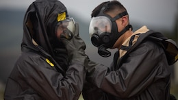 Two chemical, biological, radiological, nuclear defense specialists  ensure gas masks are properly fitted prior to leak, seal, package and decontamination training April 21 at the gas chamber on Camp Hansen, Okinawa. The CBRN defense specialists assisted in familiarizing explosive ordnance disposal technicians with decontamination procedures following the leak, seal, package process used to mitigate CBRN-related hazards.  The EOD technicians and CBRN defense specialists used protective equipment to perform general decontamination of the affected area and prepare the leaking ordnance for safe containment and transport before completing the decontamination process. The training instilled the Marines' confidence in their safety equipment and procedures used to mitigate CBRN-related hazards. The Marines are with 9th Engineer Support Battalion, and Marine Logistics Group Headquarters Regiment, 3rd MLG, III Marine Expeditionary Force.