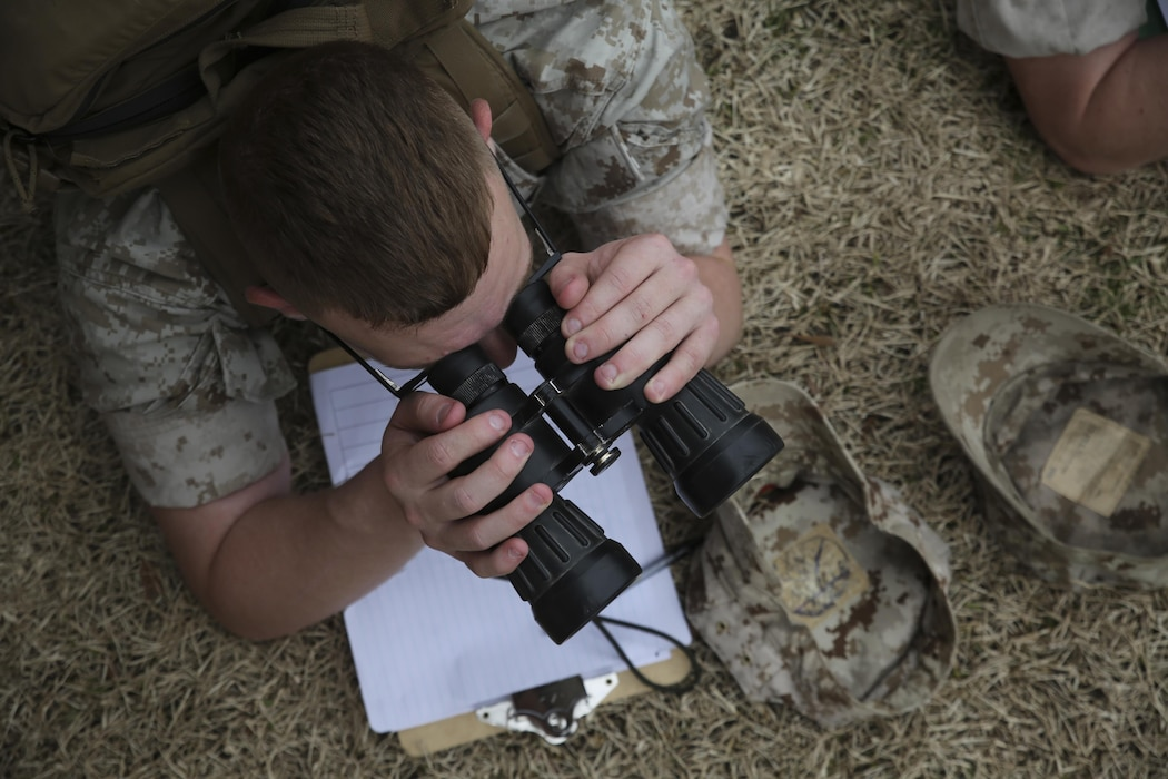 A Marine with II Marine Expeditionary Force locates practice targets using binoculars while conducting observation lane training at the Division Combat Skills Center aboard Camp Lejeune, N.C., March 9, 2015, during a designated marksmanship course. Marines use binoculars during observation lane training as part of the designated marksmanship course to aid in finding targets that are at a great distance. Observation lane training aids Marines when they later deploy to combat environments where they may encounter threats at variable distances.